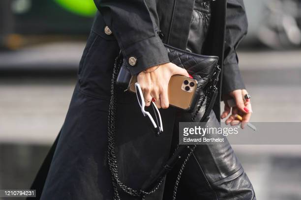 A guest wears a black leather quilted Chanel bag outside Chanel during Paris Fashion Week Womenswear Fall/Winter 2020/2021 on March 03 2020 in Paris...