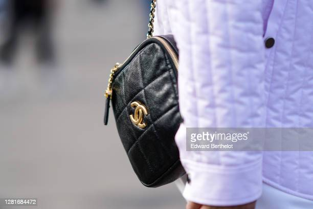 Guest wears a black leather quilted Chanel bag, outside Chanel, during Paris Fashion Week - Womenswear Spring Summer 2021, on October 06, 2020 in...