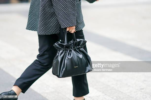 Guest wears a black leather Repetto bag, during Paris Fashion Week - Womenswear Spring Summer 2021, on October 06, 2020 in Paris, France.