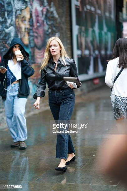 Guest wears a black leather shirt, navy blue denim pants, black shoes, a clutch, during London Fashion Week September 2019 on September 16, 2019 in...