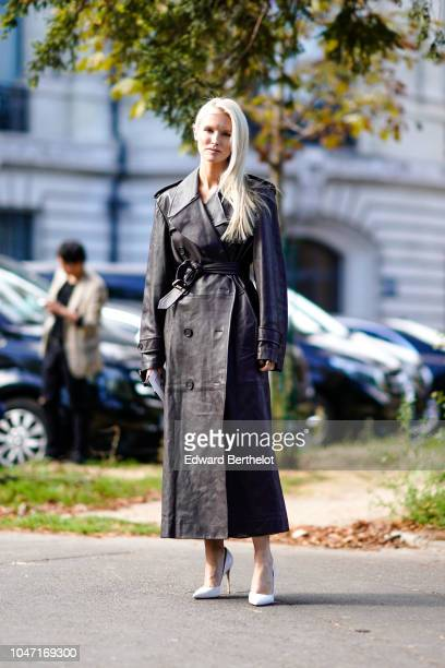 A guest wears a black leather trench coat outside Akris during Paris Fashion Week Womenswear Spring/Summer 2019 on September 30 2018 in Paris France