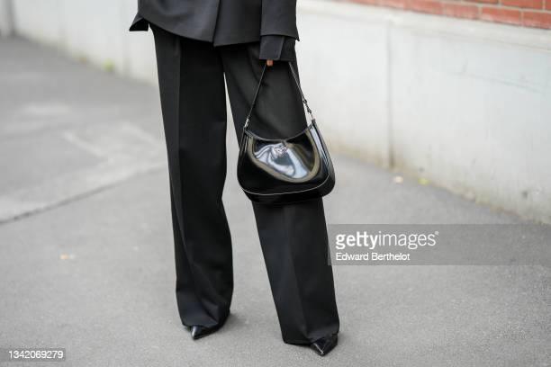 Guest wears a black long blazer jacket, black flared suit pants, a black shiny leather Prada handbag, black shiny leather pointed pumps heels shoes,...