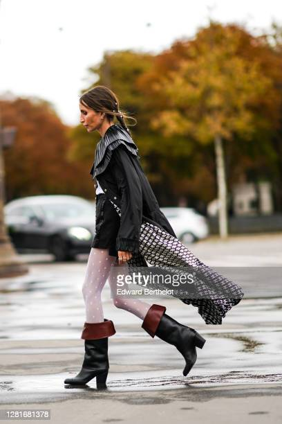 Guest wears a black long coat with large ruffle collar, a white top, black shorts, white leggigs, black and brown leather boots, outside Chanel,...