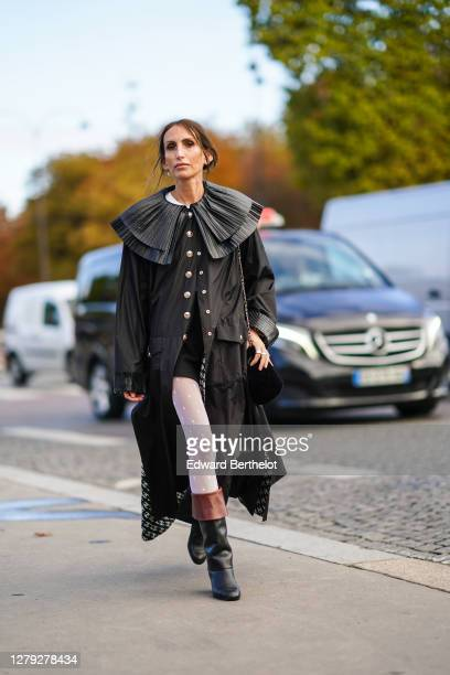 Guest wears a black long dress with large shiny ruffled collar, white leggings, black and brown leather boots, outside Chanel, during Paris Fashion...