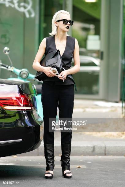 A guest wears a black low neck sleeveless top black pants sunglasses outside the Y3 show during Paris Fashion Week Menswear Spring/Summer 2018 on...