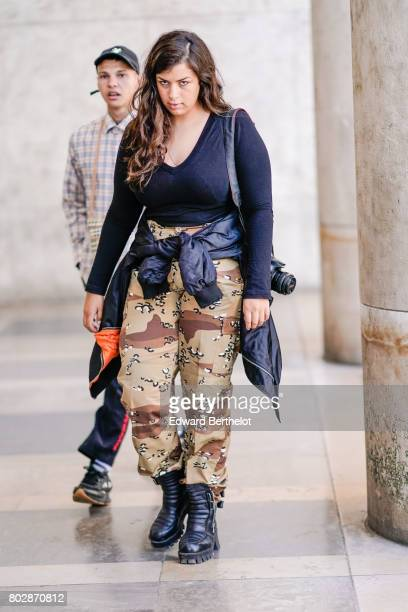 A guest wears a black low neck top military camouflage print pants black boots outside the 22/4 Hommes show during Paris Fashion Week Menswear...