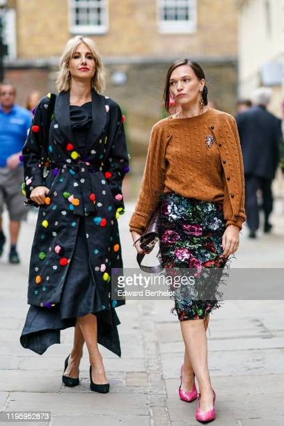 Guest wears a black lustrous kimono long jacket with colored embroidered pompoms, black high heel pumps shoes ; Anna Brewster wears a brown wool...