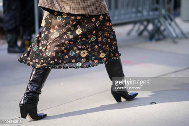 A guest wears a black mesh floral print skirt black leather boots during New York Fashion Week Fall Winter 2020 on February 12 2020 in New York City