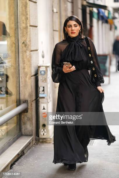 A guest wears a black mesh flowing dress earrings during Milan Fashion Week Fall/Winter 20202021 on February 23 2020 in Milan Italy