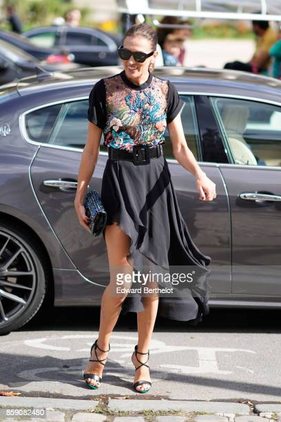 A guest wears a black mesh lace flower embroidered dress sunglasses heels outside Elie Saab during Paris Fashion Week Womenswear Spring/Summer 2018...