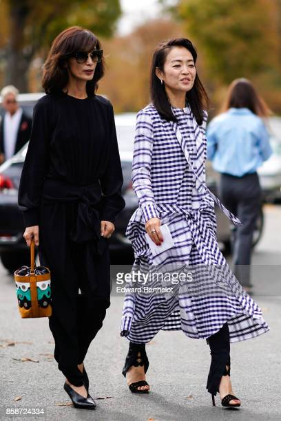 A guest wears a black outfit a guest wears a gingham dress outside Leonard during Paris Fashion Week Womenswear Spring/Summer 2018 on October 2 2017...