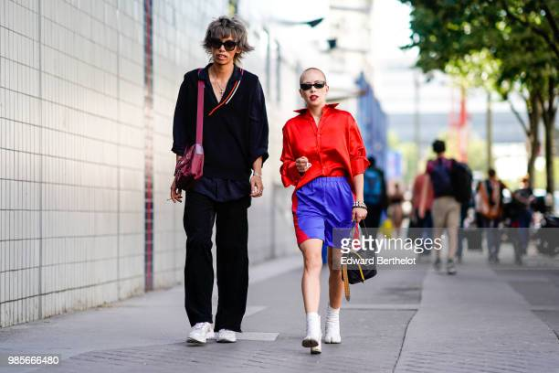 A guest wears a black outfit and a purple bag a gues wears a red shirt blue shorts white boots outside 1017 ALYX 9SM during Paris Fashion Week...