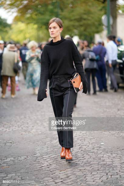 A guest wears a black oversize pull over black pants brown shoes outside CDG Comme des Garcons during Paris Fashion Week Womenswear Spring/Summer...