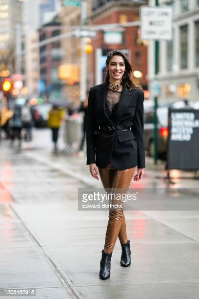 Guest wears a black oversized blazer jacket, a belt, a choker with a golden part, a black mesh top, brown shiny pvc pants, pointy leather shoes,...