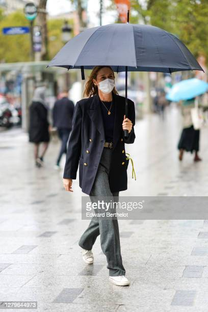 A guest wears a black oversized blazer jacket a pullover a golden necklace gray pants white sneakers a belt outside Miu Miu during Paris Fashion Week...