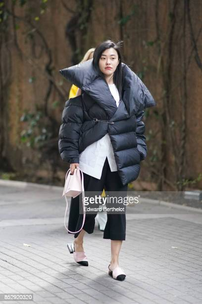 A guest wears a black oversized large puffer coat a white shirt black cropped pants sandals a pink bag during London Fashion Week September 2017 on...