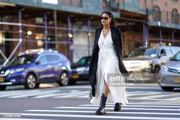 Guest wears a black oversized long jacket, a white v-neck low-neck dress, a golden necklace, black leather boots, earrings, sunglasses, outside Self...