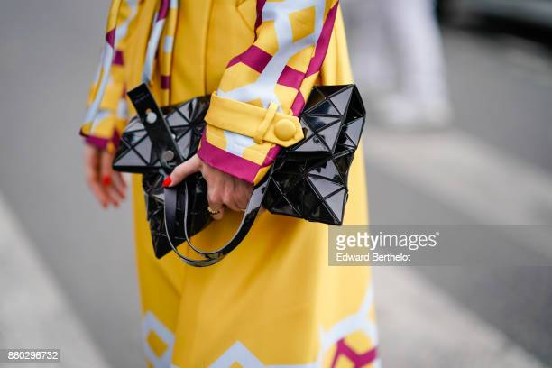 A guest wears a black patent leather geometric design bag a yellow trenchcoat with red and white geometric prints outside Lanvin during Paris Fashion...