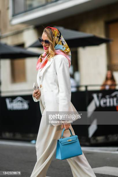Guest wears a black / pink / gold / red print pattern silk scarf, a white long blazer jacket, white latte matching flared pants, a blue shiny leather...