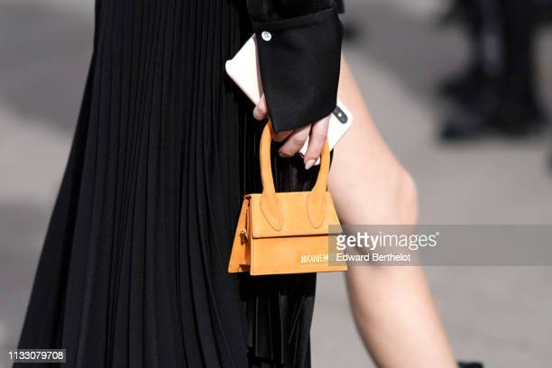 A guest wears a black pleated dress a tiny Jacquemus orange bag outside Ann Demeulemeester during Paris Fashion Week Womenswear Fall/Winter 2019/2020...