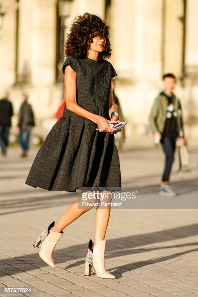 A guest wears a black pleated dress leather boots outside Louis Vuitton during Paris Fashion Week Womenswear Spring/Summer 2018 on October 3 2017 in...