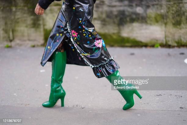 Guest wears a black pleated shiny skirt with colored floral print, green leather high boots, outside Elie Saab, during Paris Fashion Week -...