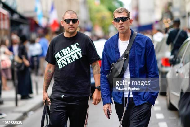 A guest wears a black 'public enemy' tshirt a guest wears a blue jacket sunglasses a fanny pack shoulder strapped bag a white tshirt outside Yohji...