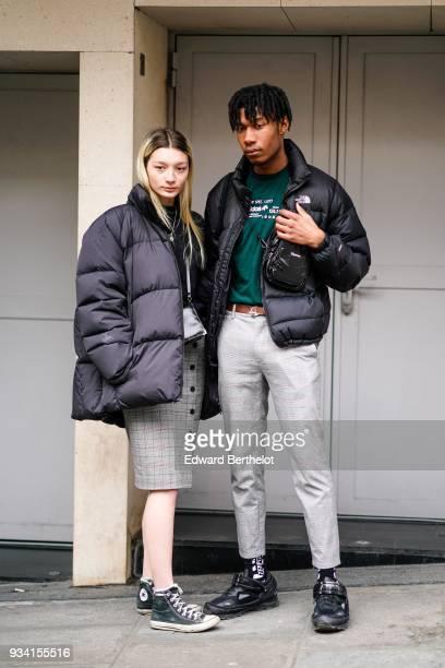 A guest wears a black puffer a grey geometrical pattern button front skirt black sneakers a guest wears a black puffy jacket a green top a brown belt...