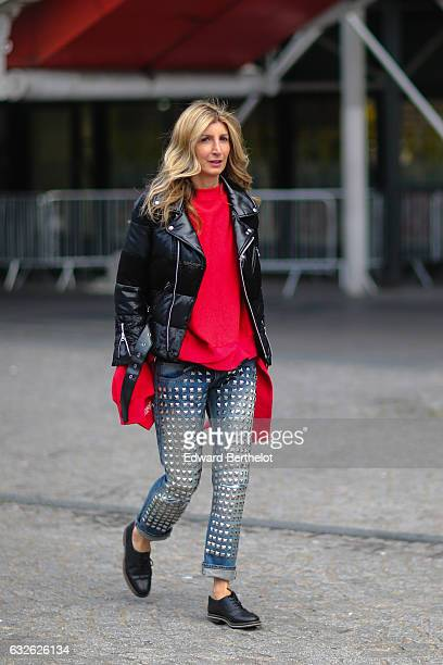 A guest wears a black puffer jacket a red top and blue denim jeans outside the Vetements show at Centre Pompidou during Paris Fashion Week Haute...