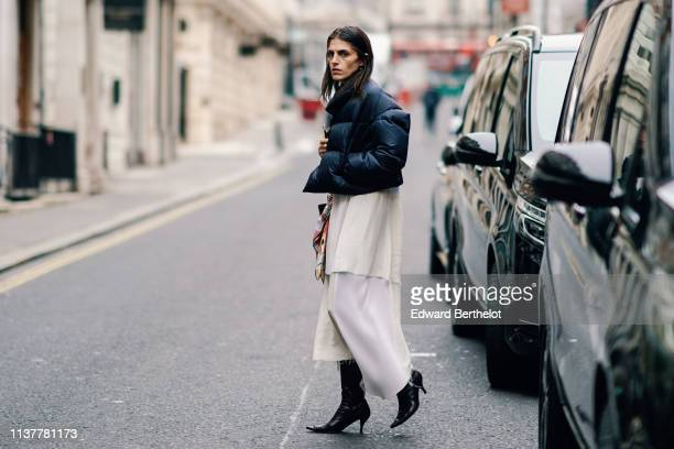 A guest wears a black puffer jacket a white rippedhem maxiskirt black heeled pointy pumps during London Fashion Week February 2019 on February 16...