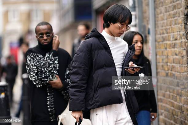 Guest wears a black puffer jacket, glasses, during London Fashion Week Men's January 2019 on January 05, 2019 in London, England.