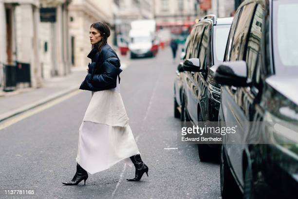 A guest wears a black puffer spencer jacket a white rippedhem maxiskirt black heeled pointy pumps during London Fashion Week February 2019 on...