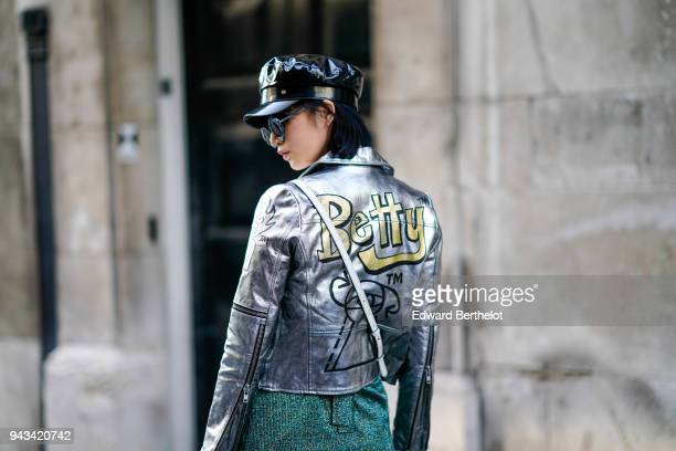 A guest wears a black pvc cap a shiny siler jacket with a printed 'BETTY' during London Fashion Week February 2018 on February 16 2018 in London...