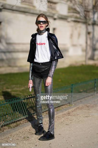 A guest wears a black pvc shiny jacket a white tshirt sunglasses a choker glitter pants during Paris Fashion Week Womenswear Fall/Winter 2018/2019 on...