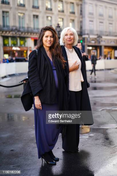 A guest wears a black quilted bag a black jacket a purple lowcut empirewaist long dress black pumps outside the Opera Garnier 350th Anniversary Gala...