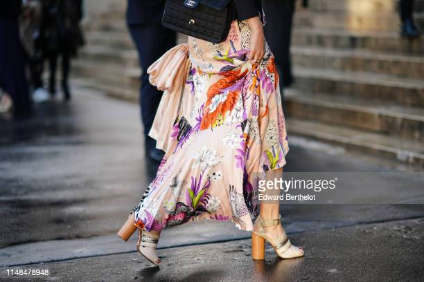 Guest wears a black quilted Chanel bag, a colorful floral print flowing skirt, beige sandals with cylindrical heels, outside the Opera Garnier 350th...