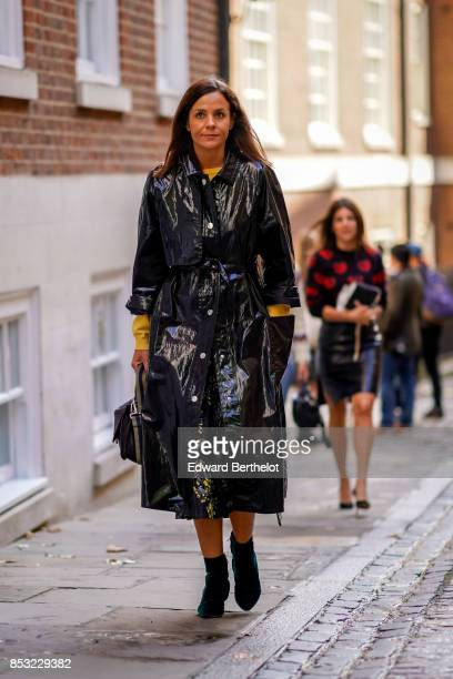 A guest wears a black rain coat during London Fashion Week September 2017 on September 16 2017 in London England