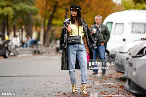 A guest wears a black raincoatblue jeans black Chanel bag black hat yellow pussy bow top and highheeled gold lame sandals outside Manish Arora during...
