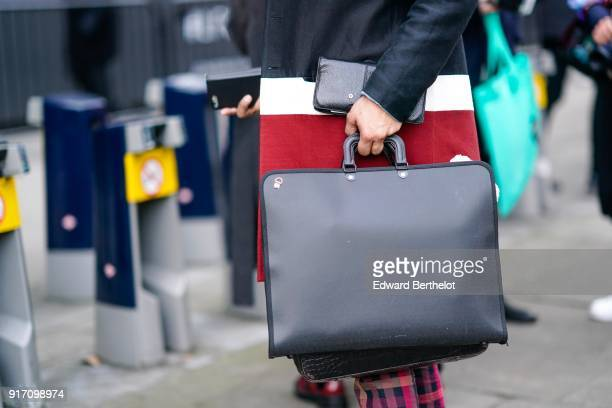 A guest wears a black rectangular bag during London Fashion Week Men's January 2018 at on January 6 2018 in London England