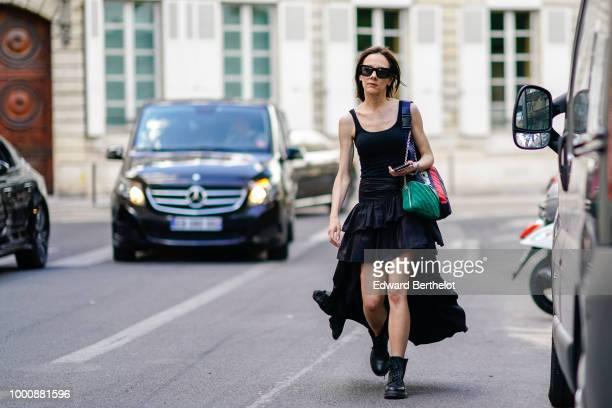 A guest wears a black ruffled dress black leather boots a green bag during Paris Fashion Week Menswear SpringSummer 2019 on June 22 2018 in Paris...