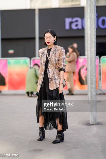 A guest wears a black ruffled pleated asymmetric dress a camel tartan jacket black ankle boots outside Chloe during Paris Fashion Week Womenswear...