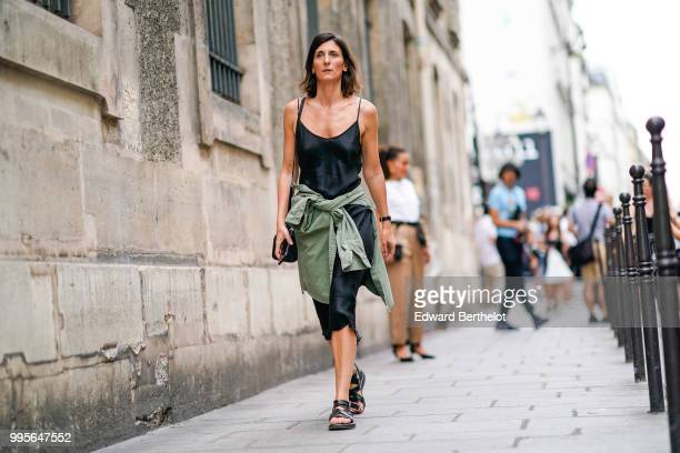 A guest wears a black satin dress and a green pull over outside Givenchy during Paris Fashion Week Haute Couture Fall Winter 2018/2019 on July 1 2018...