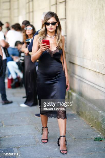 Guest wears a black satin dress with lace, sunglasses, earrings, necklace, shoes outside Valentino, during Paris Fashion Week -Haute Couture...