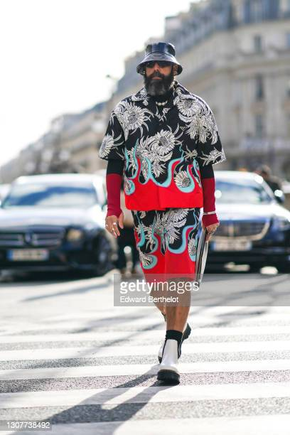 Guest wears a black shiny leather bob hat, black sunglasses, a Prada oversized floral print black white blue and red shirt, a pearl necklace, Prada...