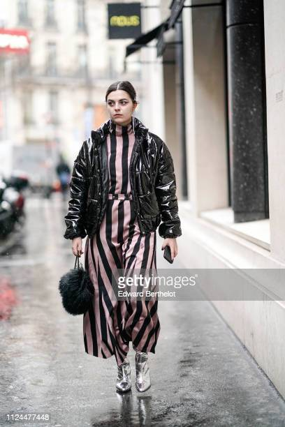 Guest wears a black shiny puffer jacket, a pink and black striped dress, silver shoes, during Paris Fashion Week - Haute Couture Spring Summer 2020,...
