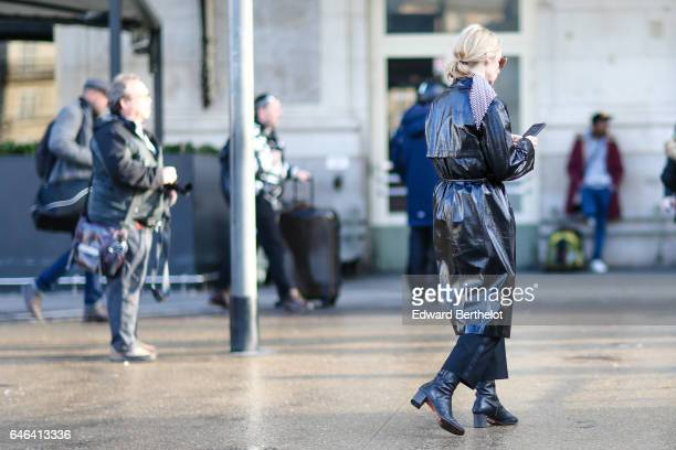A guest wears a black shiny raincoat outside the Olivier Theyskens show during Paris Fashion Week Womenswear Fall/Winter 2017/2018 on February 28...