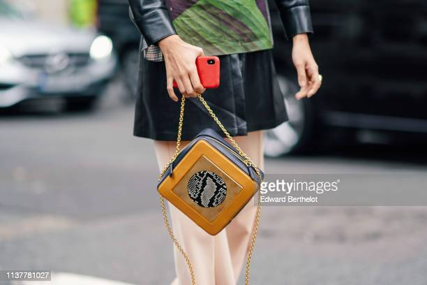 A guest wears a black shiny tunic a banana leaves print fitted top peachcolor pants a black and orange bag with a round grey python pattern insert...