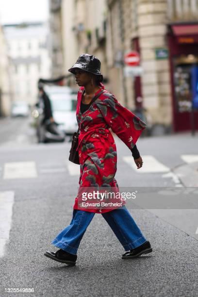 Guest wears a black shiny vinyl hat, a red floral print kimono dress, blue flared denim jeans pants, black leather shoes, earrings, outside ETUDES,...