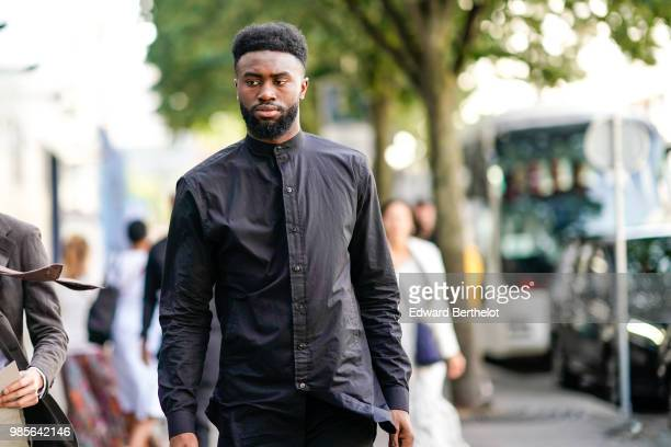 A guest wears a black shirt outside 1017 ALYX 9SM during Paris Fashion Week Menswear SpringSummer 2019 on June 24 2018 in Paris France
