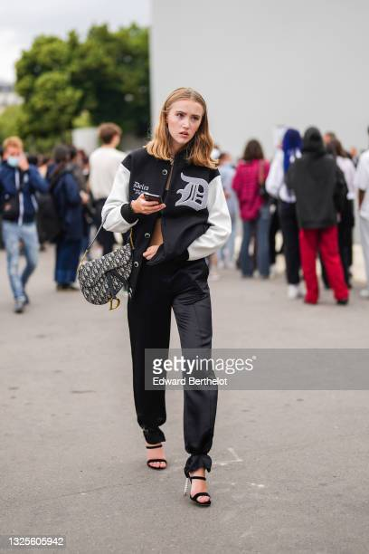 Guest wears a black shoulder-off crop-top, a black with white leather sleeves teddy jacket with a pale gray fluffy inscription and logo, a silver...